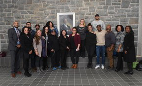 "IB&M Director, Prof. Michelle Williams, Assistant, Valerie Armstrong, students and alumni with the portrait of the late Dr. Burnley ""Rocky"" Jones"